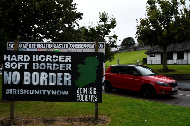 A car drives past a sign saying 'No Border, Hard border, soft border, no border' in Londonderry