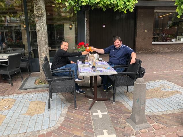 El autor del blog y un amigo brindando en una mesa situada exactamente sobre la frontera entre Bélgica y Holanda